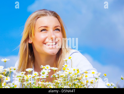 Closeup portrait of cute blond female on daisy meadow over blue sky background, spring season, happiness concept - Stock Photo