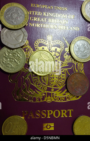An image of the front page of a British passport covered in coins from the UK and Europe. - Stock Photo