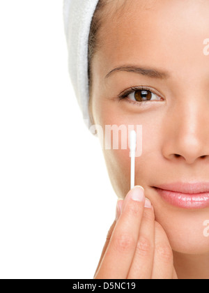 Closeup portrait of smiling beautiful mixed race young woman showing cotton swab on face isolated on white background - Stock Photo