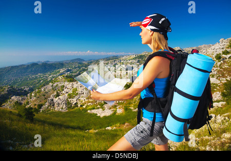 Active young girl searching right track on the map, traveling to high mountains, beautiful landscape, extreme lifestyle - Stock Photo