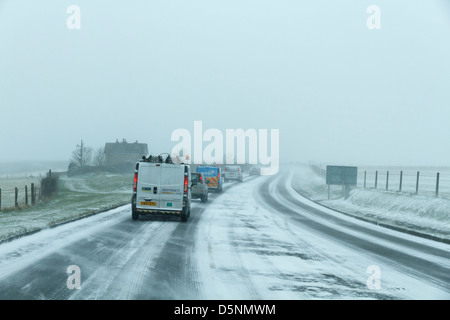 dangerous driving conditions rta road traffic accident snow snowy ice icy blizzard covered slippery police ambulance - Stock Photo