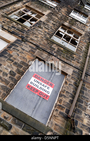 Danger unsafe building keep out sign on a disused mill building in Lancashire, England. - Stock Photo