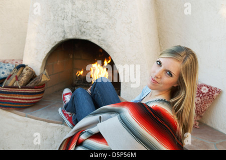 21 year old woman in front of outdoor southwest fireplace - Stock Photo