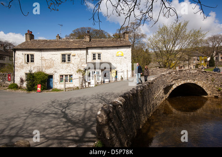 UK, England, Yorkshire, Malham, village shop beside old stone bridge across River Aire - Stock Photo