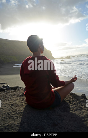 Young attractive woman meditates in lotus pose, in front of the coast. - Stock Photo