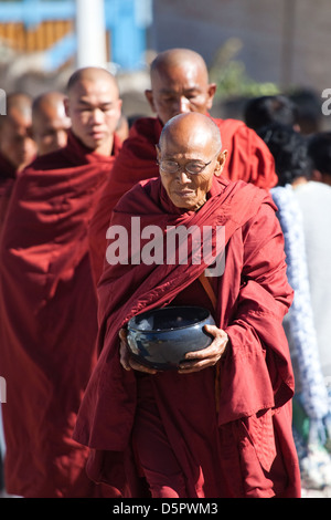 Burmese monks collecting their alms - Stock Photo