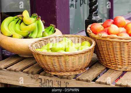 Baskets of Fruit, bowls of apples, pears and bananas on a wooden table - Stock Photo