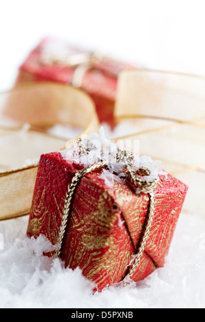 Little chistmas presents on white reflective table - Stock Photo