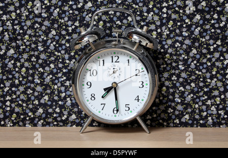Old style alarm clock, on a dresser in front of floral wallpaper. Time set at 7.30 - Stock Photo