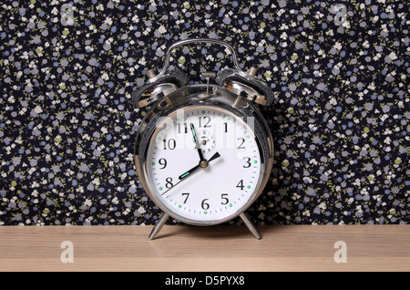 Old style alarm clock, on a dresser in front of floral wallpaper. Time set at just before 8. - Stock Photo