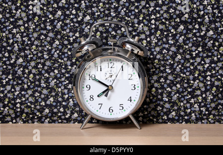 Old style alarm clock, on a dresser in front of floral wallpaper. Time set at 7.50. - Stock Photo