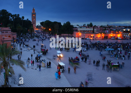 Djemaa el Fna, the main square in Marrakech, Morocco, at dusk, with the minaret of the Koutoubia Mosque in the background. - Stock Photo