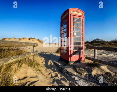 Old red phone box on the beach at Studland in Dorset - Stock Photo