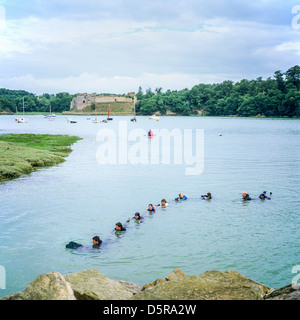 Exercise with a Newfoundland rescue dog pulling 7 people in 'Arguenon' river Brittany France Europe - Stock Photo