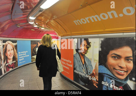 Oxford Circus station, London, UK. 8th April 2013. Commuters and tourists pass by the posters in the underground - Stock Photo