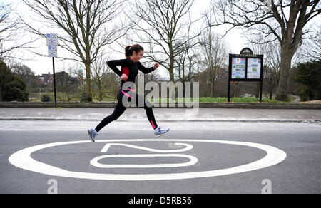 Brighton, Sussex, UK. 8th April 2013. A runner speeds past one of the new 20mph limit road marking signs in the - Stock Photo