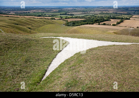 The Uffington White Horse, a prehistoric figure carved in chalk overlooking The Manger and Dragon Hill below. - Stock Photo
