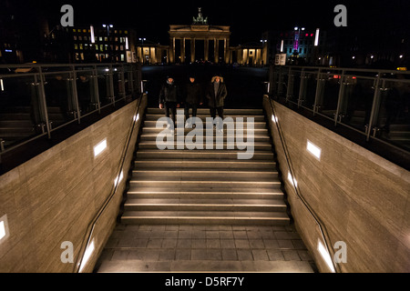 Three men go down to the metro station at Brandenburg Gate, Berlin, Germany. - Stock Photo
