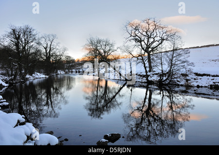 Evening River Wharfe near Hebden North Yorkshire England, in snow. reflections in the river. - Stock Photo