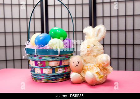 Sad egg on bunny's lap. - Stock Photo