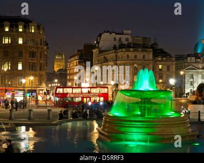 Trafalgar Square fountains lit up at night with red bus and Whitehall behind West End London UK - Stock Photo
