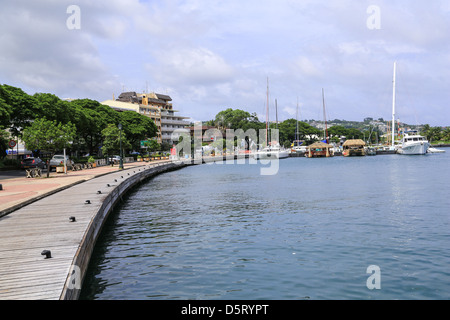 The waterfront boardwalk curves toward boats moored in the harbour at Papeete, Tahiti. - Stock Photo