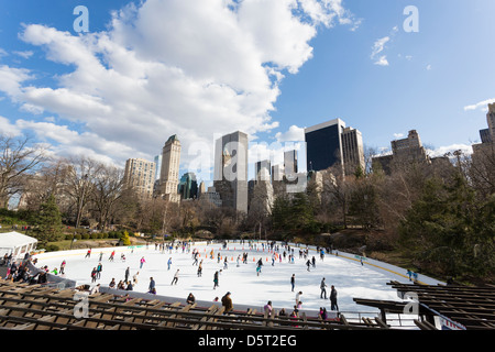 People skating on a ice ring in Central Park, New York City with buildings in the background - Stock Photo