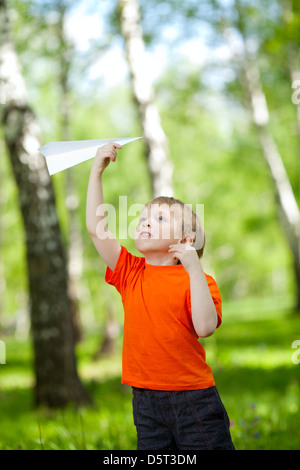 Cute boy holding a paper airplane in park - Stock Photo