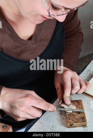 Close-up image of a female jeweler filing a piece of metal in her workshop. - Stock Photo
