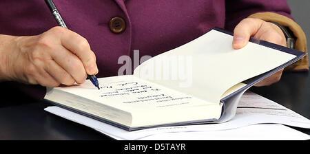German Chancellor Angela Merkel signs the book 'Dialog über Deutschlands Zukunft' ('Dialogue about the Future of - Stock Photo