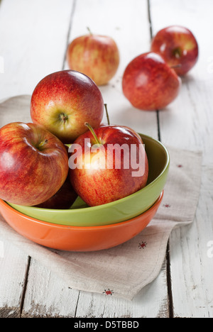 several of red apples in colour plates on the white kitchen table - Stock Photo