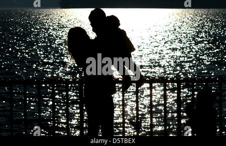 The silhouette of a woman and child are pictured in the back-lighting at Maschsee Lake in Hanover,Germany, 20 November - Stock Photo