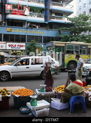Fruit and vegetable vendors line the Bandoola Road in front of a building in Yangon, Myanmar, 21 October 2012. A - Stock Photo