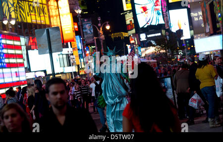 People walk along Times Square in New York, USA, 26 September 2012. Times Square is located at the intersection - Stock Photo