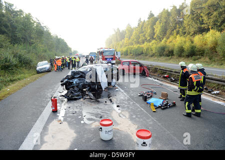 Emergency workers stand next to two severely damaged car after a ghost driver crash onAutobahn 73 near Hirschaid,Germany, - Stock Photo