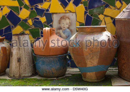 Mixed old pots jugs and vases on a low brick wall backed by a mosaic of blue yellow and green tiles. - Stock Photo