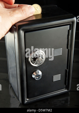 Male hand putting money in a black strongbox over black background - Stock Photo
