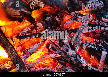 natural wood log fire embers glowing great for background or in solid fuel stoves now classed as a renewable power - Stock Photo