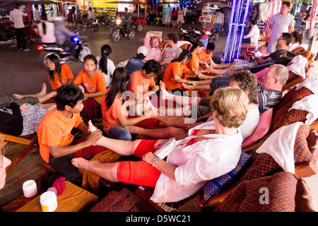 Masseurs and masseuses massage tourists on street at night in Pub Street nightlife district Siem Reap Cambodia - Stock Photo