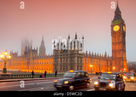 Westminster Palace and Big Ben with london cabs in foreground at dusk - Stock Photo