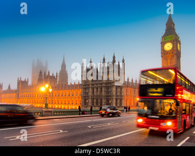 Houses of Parliament and Big Ben with a red double decker bus and black london taxi in the evening light - Stock Photo