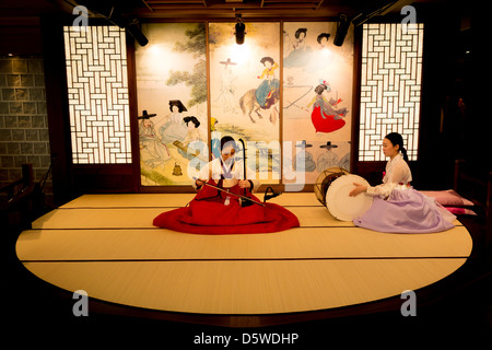 Korean women play traditional music and song in departure lounge of Inchon Airport Seoul South Korea to entertain - Stock Photo