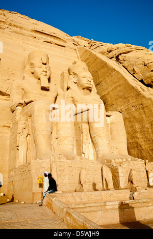 Two of the four statues of Pharaoh Ramesses II outside the Great Temple in Abu Simbel, Egypt - Stock Photo