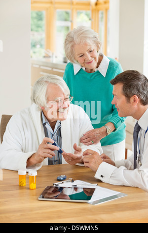 Doctor talking with older patient and wife - Stock Photo