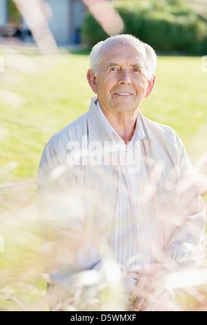 Older man standing in backyard - Stock Photo