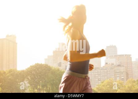 Woman running in urban park - Stock Photo