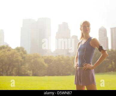 Runner standing in urban park - Stock Photo