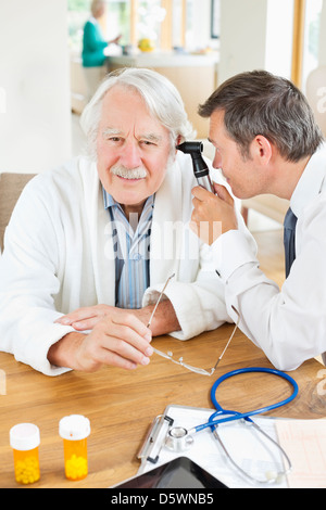 Doctor examining older man's ear at house call - Stock Photo