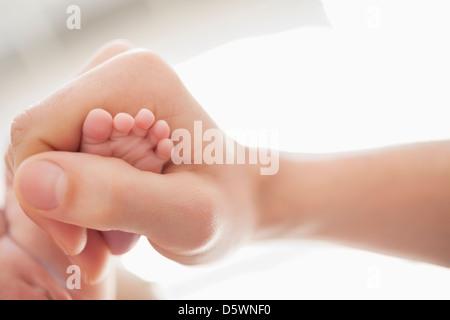 Mother cradling newborn baby's foot - Stock Photo