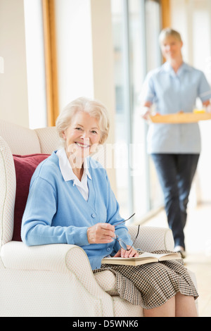 Older woman smiling in armchair - Stock Photo